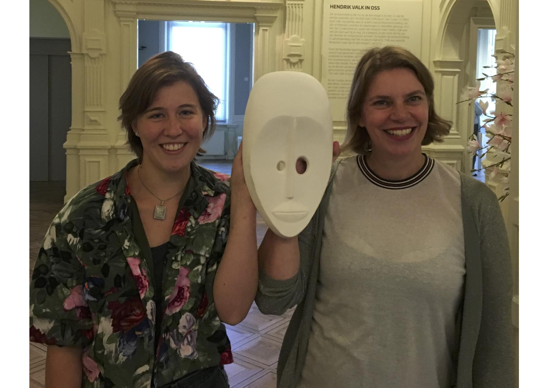 Anne Giesen en Marijke van Doorn met het masker dat ten grondslag ligt aan de tentoonstelling 'Sign of the Times - Gemaskerd Bal van de hedendaagse kunst'